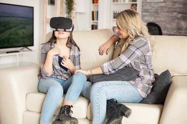 Menina bonitinha usando fone de ouvido de realidade virtual para jogar videogame. bela jovem mãe. garoto feliz.