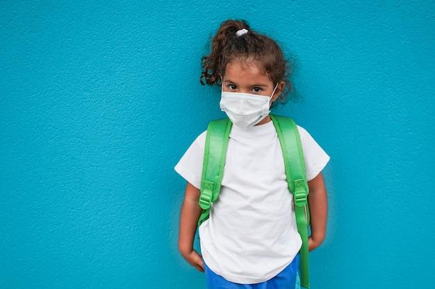 Menina bonitinha usando máscara de proteção contra coronavírus a caminho do jardim de infância - criança pré-escolar