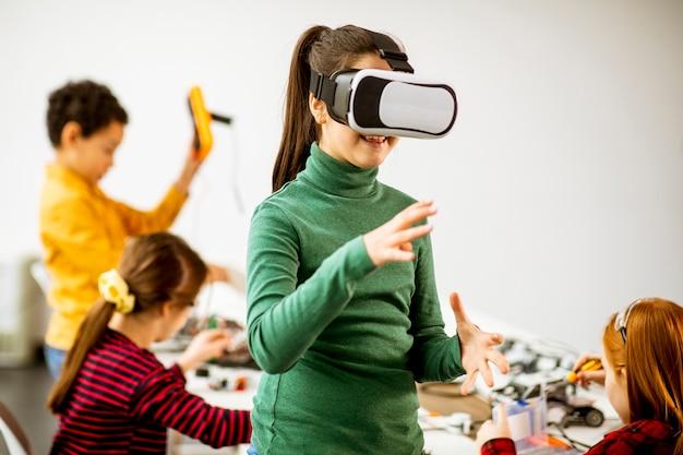 Menina bonitinha usando óculos de realidade virtual de rv em uma sala de aula de robótica