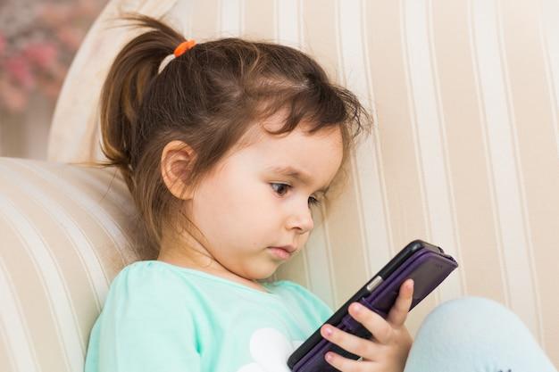 Menina bonitinha usando smartphone moderno