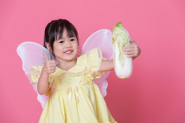 Menina bonitinha vestir-se como um anjo com asas brancas, mantendo o repolho e o polegar. conceito de comer e estilo de vida saudável. comida vegetariana verde