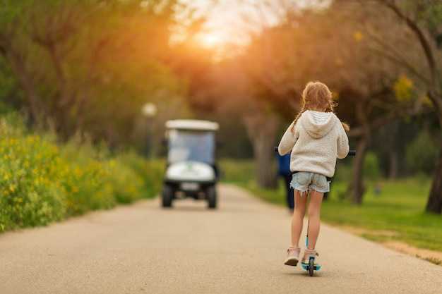 Menina bonito 5-6 anos andando de scooter ao ar livre sobre a natureza