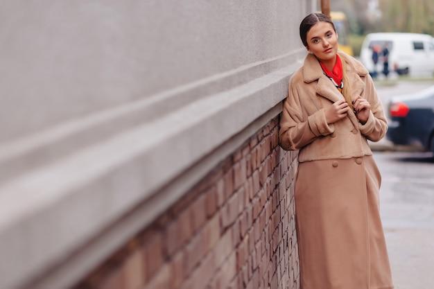 Menina bonito à moda nova em um casaco de pele que dá uma volta em torno da cidade perto das casas de madeira e das paredes de pedra