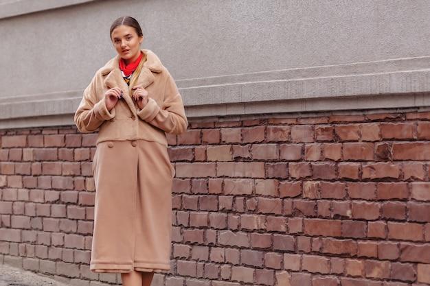 Menina bonito à moda nova em um casaco de pele que dá uma volta em torno da cidade perto das casas de madeira
