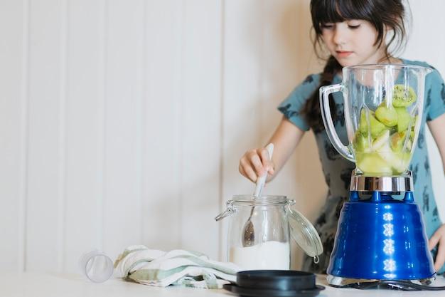 Menina bonito adicionando açúcar ao liquidificador