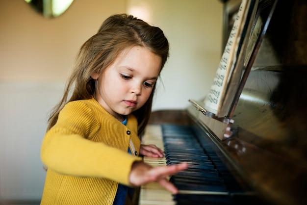 Menina bonito adorável que joga o conceito do piano