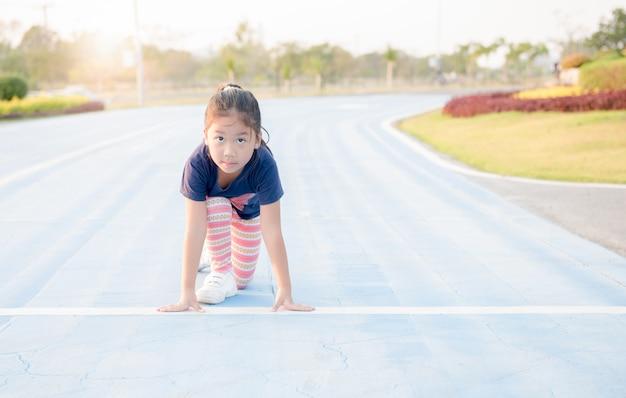 Menina bonito alegre em posição pronta para correr na pista