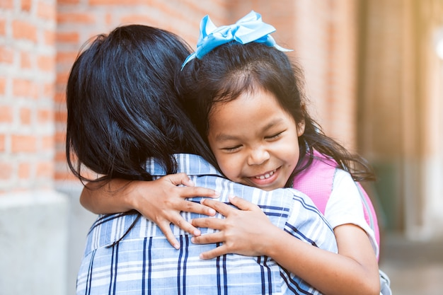 Menina bonito aluno asiático com mochila abraçando sua mãe com a felicidade depois de volta da escola