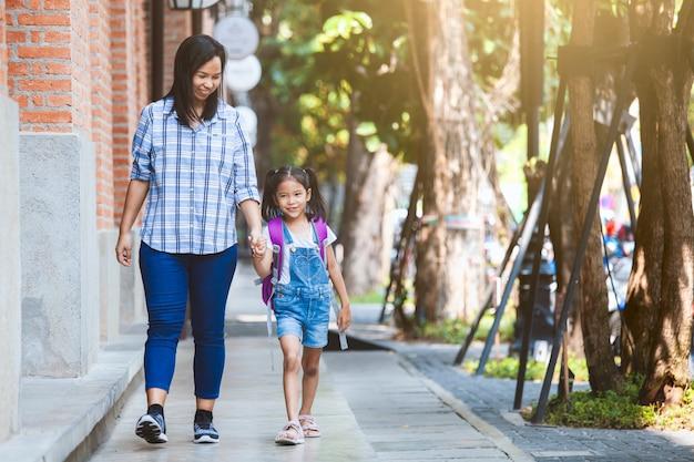 Menina bonito aluno asiático com mochila segurando a mão da mãe e ir para a escola