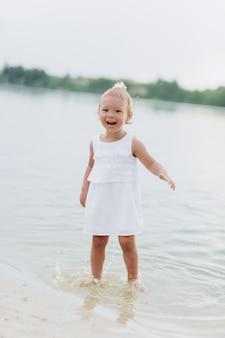 Menina bonito andando e se divertindo na praia perto do lago. o conceito de férias de verão. dia do bebê família a passar tempo juntos na natureza.