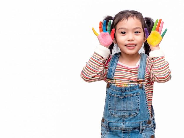 Menina bonito asiática engraçada que joga a pintura da aguarela nas mãos.