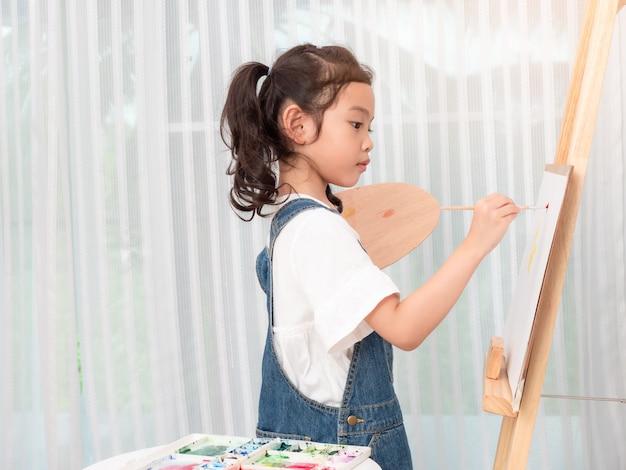 Menina bonito asiática pequena 6 anos que jogam aquarelas da pintura no livro branco.