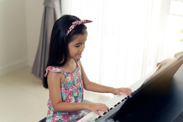 Menina bonito asiática pequena nova que joga o piano eletrônico em casa.