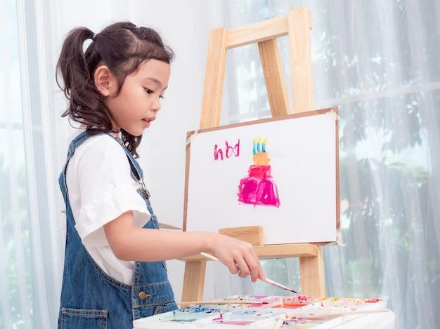 Menina bonito asiática pequena que joga as aquarelas que pintam o bolo para o feliz aniversario no livro branco.