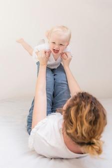 Menina bonito, brincando com a mãe em casa