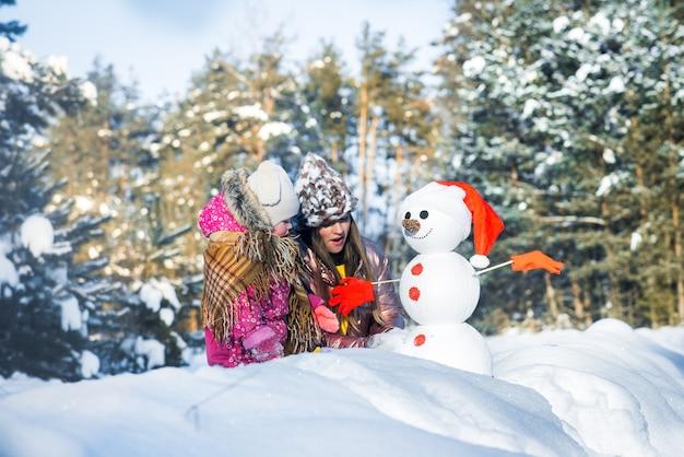 Menina bonito com a mãe faz um boneco de neve na floresta gelada. atividades ao ar livre no inverno.