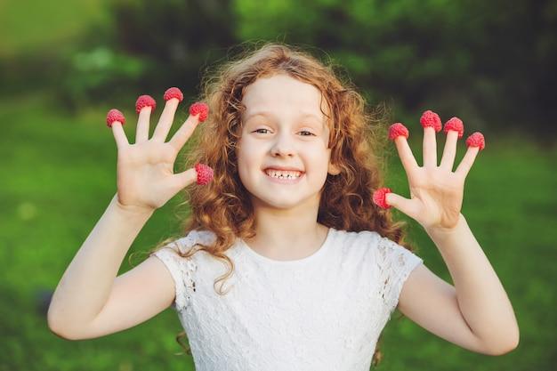 Menina bonito com as framboesas em seus dedos que mostram seus dentes.