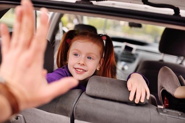 Menina bonito com cabelo vermelho, sorrindo para o interior do carro