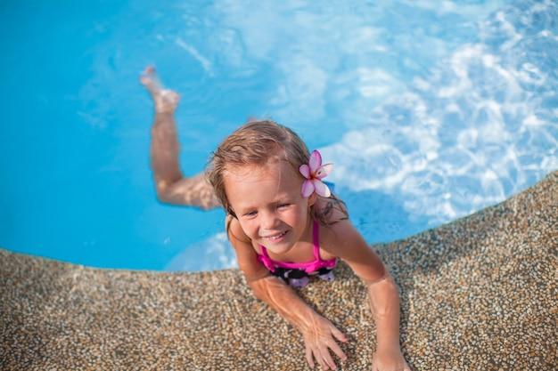 Menina bonito com flor atrás da orelha na piscina