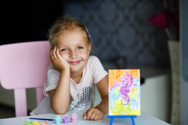 Menina bonito com imagem da pintura do cabelo louro em casa.