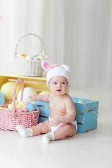 Menina bonito com os ovos da páscoa que sentam-se no assoalho em casa.