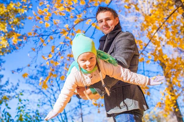 Menina bonito com pai feliz se divertindo no parque do outono em um dia ensolarado