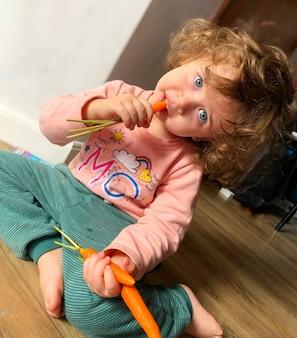 Menina bonito comendo cenouras.