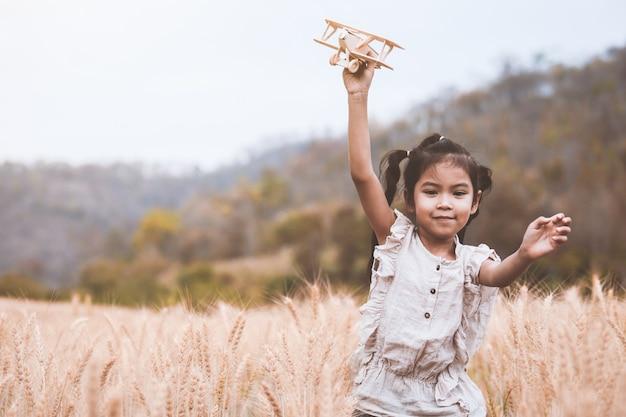 Menina bonito criança asiática correndo e brincando com o avião de brinquedo de madeira no campo de cevada