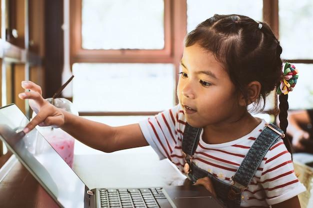Menina bonito criança asiática usando e jogando no laptop no café com diversão e felicidade