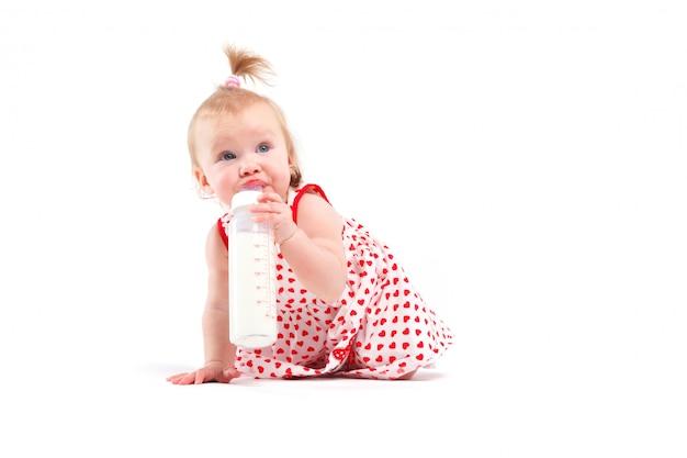 Menina bonito da beleza no vestido vermelho segurar a garrafa de leite