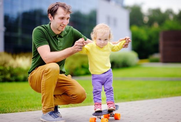 Menina bonito da criança aprendendo a andar de skate com o pai ao ar livre