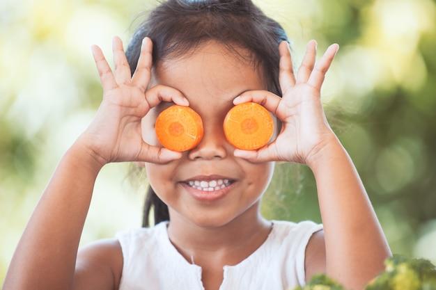 Menina bonito da criança asiática se divertindo para aprender sobre legumes com felicidade