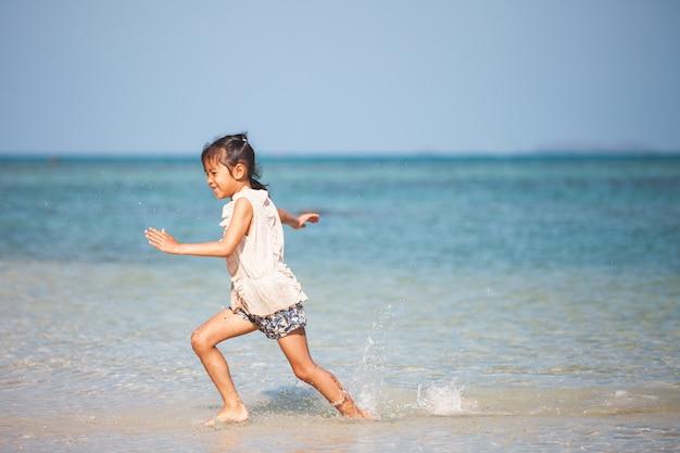 Menina bonito da criança asiática se divertindo para jogar e correr na praia perto do lindo mar em férias de verão