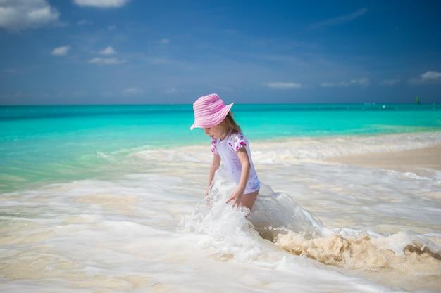 Menina bonito da criança brincando na água rasa na praia exótica