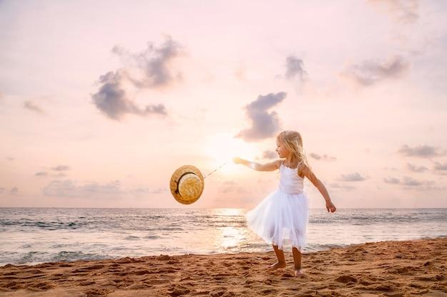 Menina bonito da criança com cabelo louro em um vestido branco do tutu que anda em uma praia arenosa no por do sol.