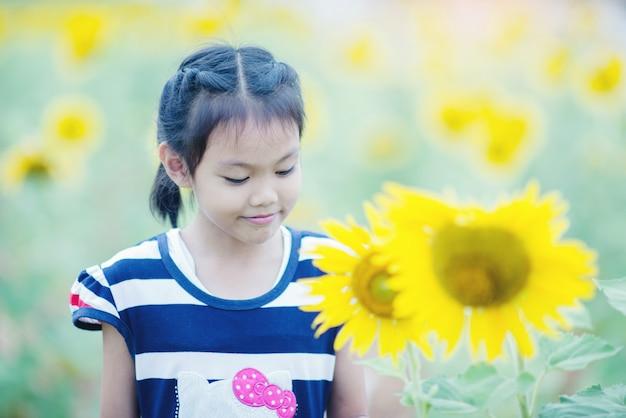 Menina bonito da criança com girassol no campo de verão