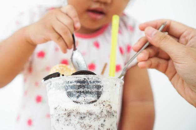 Menina bonito da criança pequena que come o leite de orio em um vidro.