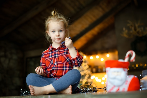 Menina bonito da criança que come o ovo de chocolate que senta-se em uma casa de caça decorada para o natal.