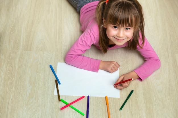Menina bonito da criança que desenha com os lápis de cor lápis coloridos no livro branco. arte educação, conceito de criatividade.