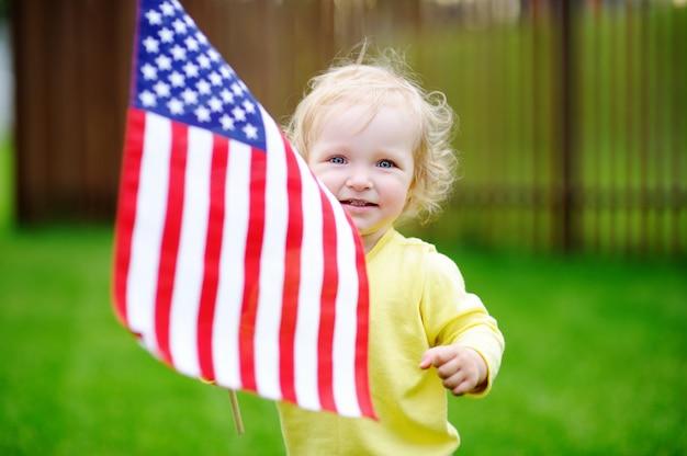 Menina bonito da criança que guarda a bandeira americana.