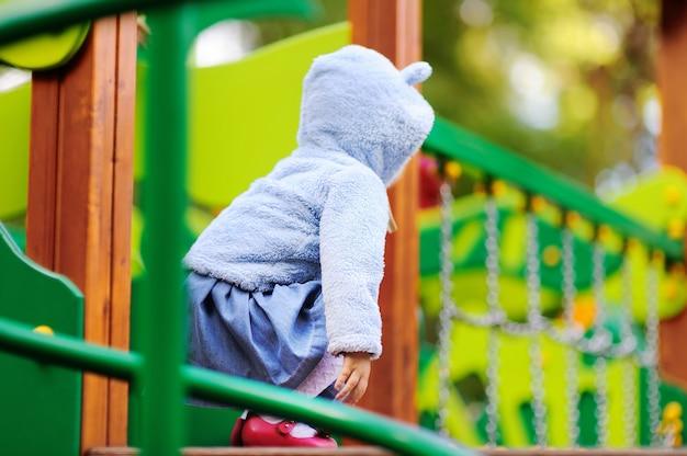 Menina bonito da criança se divertindo no playground ao ar livre