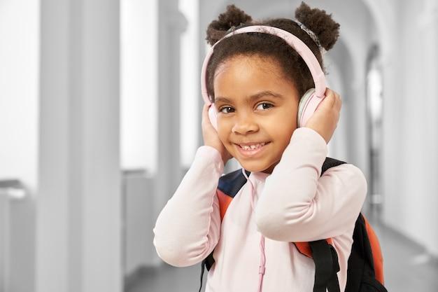 Menina bonito da escola segurando grandes fones de ouvido rosa