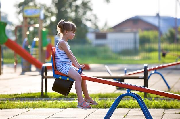 Menina bonito da jovem criança ao ar livre no balanço da gangorra no dia de verão ensolarado.