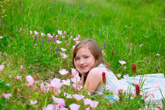 Menina bonito de crianças na primavera prado com flores de papoula