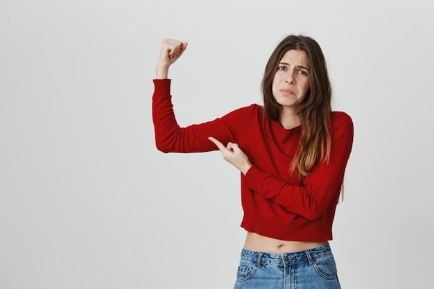 Menina bonito desapontado flex bíceps e fazer caretas, sentindo a semana, precisa comprar academia