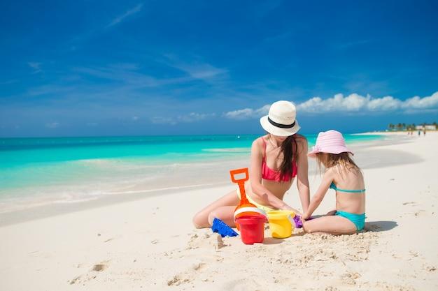 Menina bonito e mãe nova que constroem o sandcastle na praia tropical
