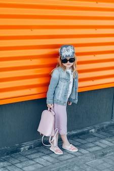 Menina bonito elegante em óculos de sol pretos na saia rosa com bolsa rosa