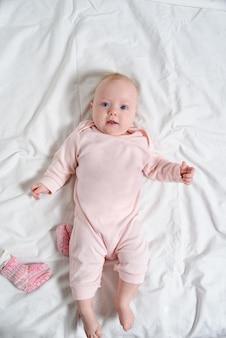 Menina bonito em um terno rosa sorrindo. deitado em um lençol branco