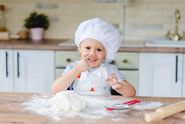 Menina bonito em uma fantasia de chef está cozinhando na cozinha