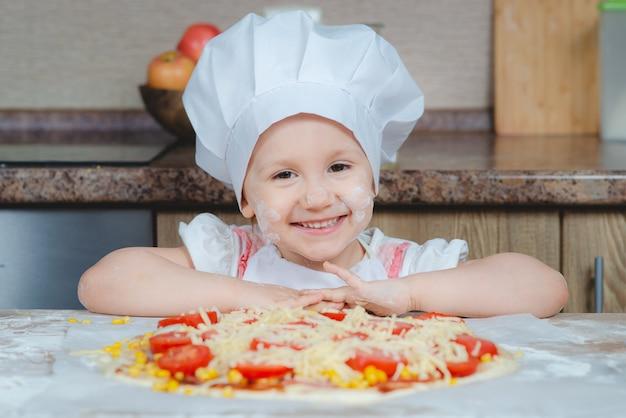 Menina bonito em uma fantasia de chef na cozinha com pizza